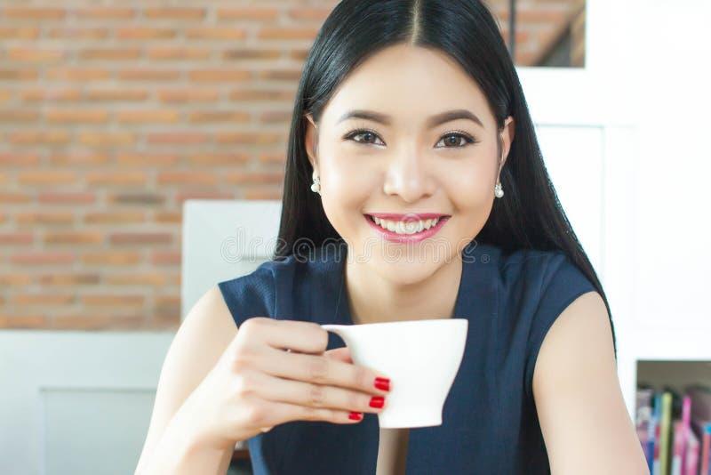Azjatycka kobieta pije kawę z uśmiechem na jej twarzy obraz stock