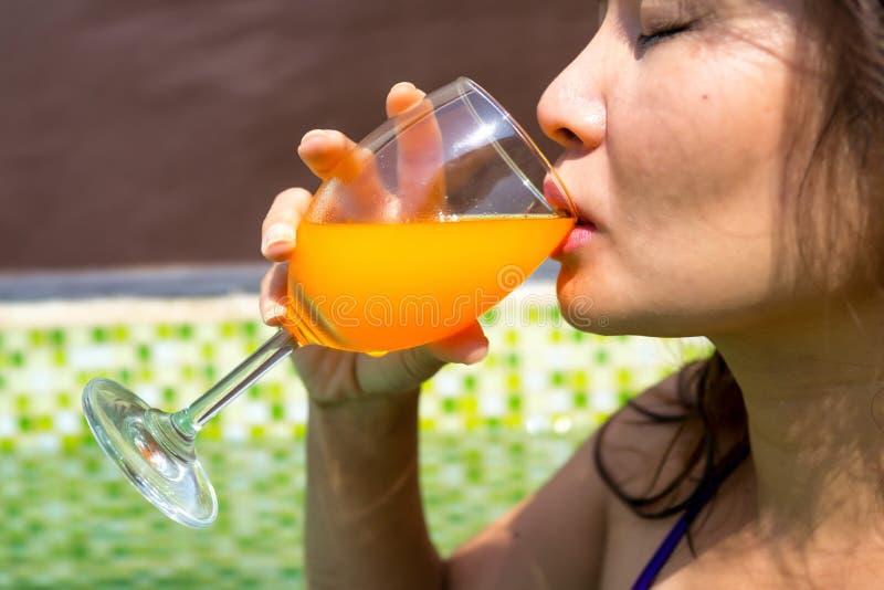 Azjatycka kobieta pije szkło zimny sok pomarańczowy w pływackim basenie zdjęcia stock