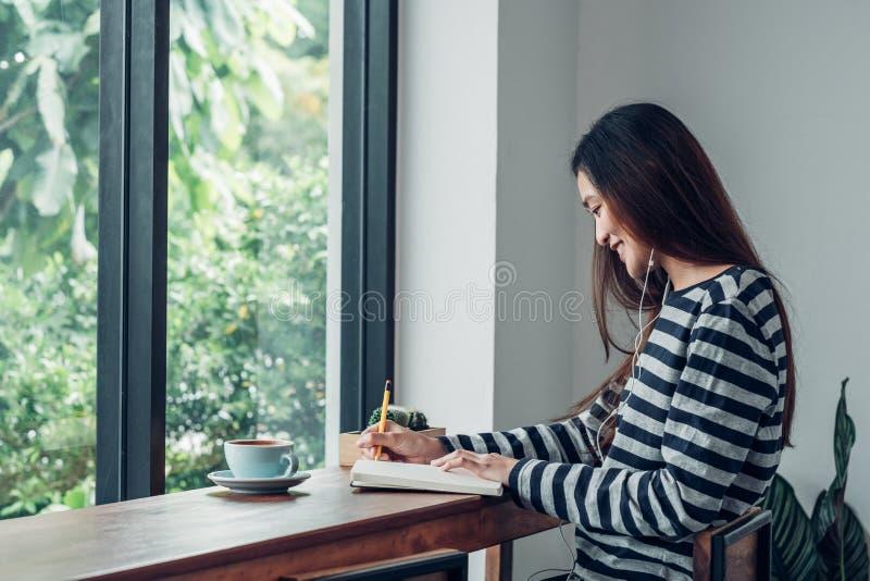Azjatycka kobieta pisze książkowej słuchającej muzyce z mobilnym obsiadaniem przy cukiernianym restauracyjnym pobliskim okno widz obraz royalty free