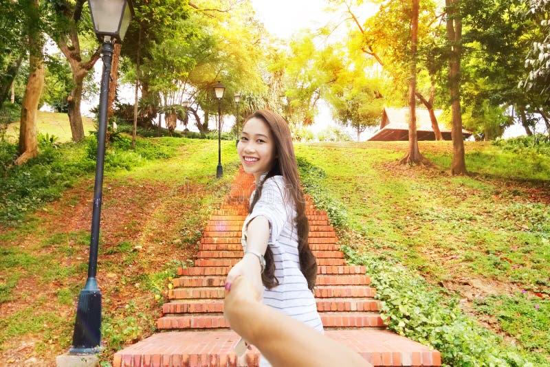 Azjatycka kobieta podąża ja mienie mężczyzna ręki szczęśliwy uśmiech fotografia stock