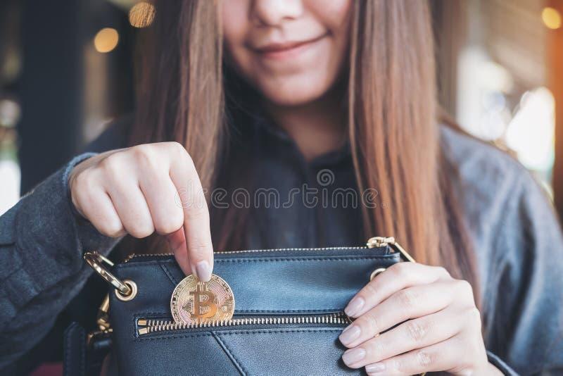 Azjatycka kobieta podnosi up bitcoin i opuszcza w czarnego portfel obraz royalty free