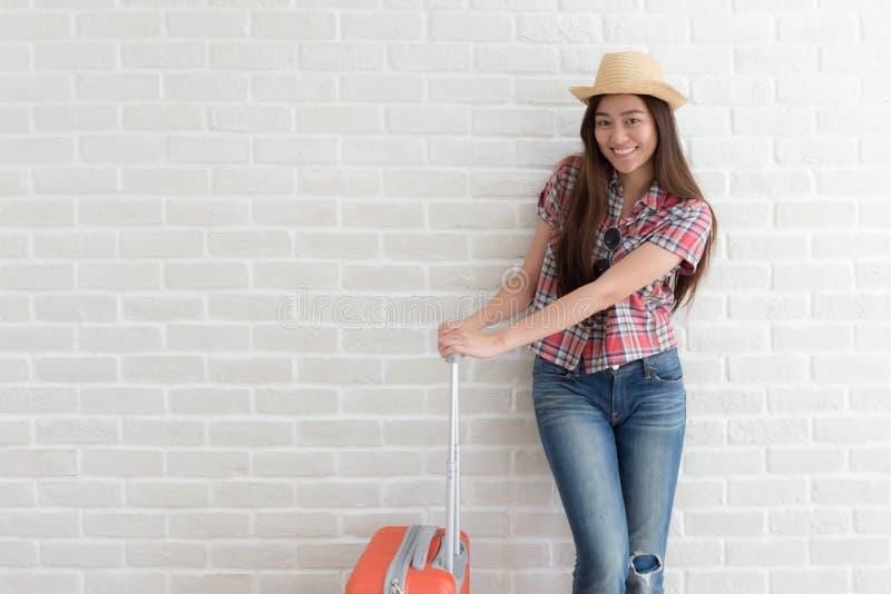 Azjatycka kobieta przygotowywa podróżować na białej ścianie z cegieł, styl życia i turystyce, fotografia royalty free