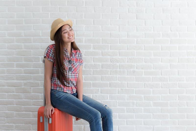 Azjatycka kobieta przygotowywa podróżować na białej ścianie z cegieł, Lifest zdjęcia royalty free