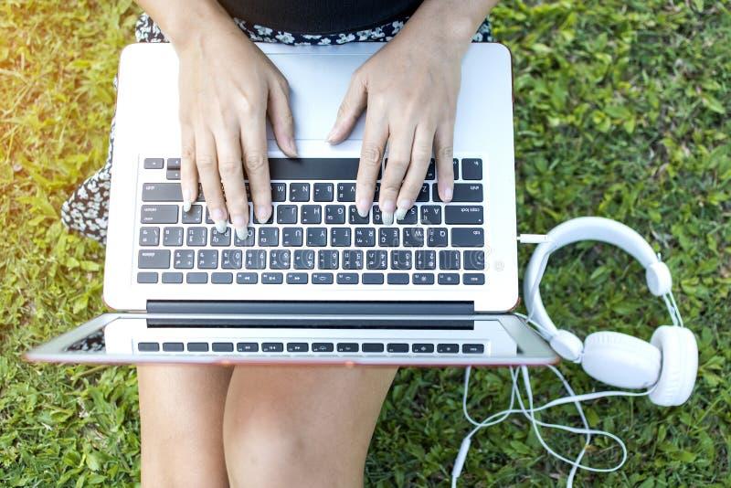 Azjatycka kobieta relaksuje siedzieć na trawie używać laptop podczas gdy naciskający Tajlandzką klawiaturę na notatniku i stawiaj zdjęcia stock