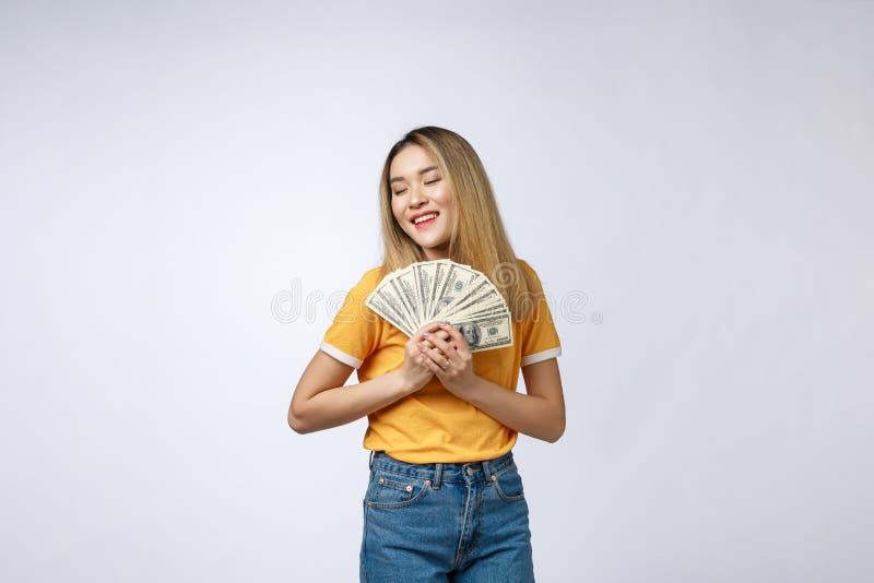 Azjatycka kobieta trzyma gotówkowe notatki odizolowywać w białym tle Młoda azjatykcia kobieta w białej koszulce w wygranie niespo zdjęcie stock