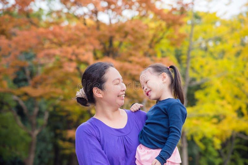 Azjatycka kobieta trzyma jej córki i ono uśmiecha się wpólnie fotografia stock