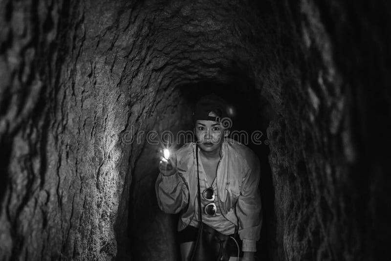 Azjatycka kobieta trzyma małą pochodnię w ciemnym starym kopalnianym tunelu obrazy stock