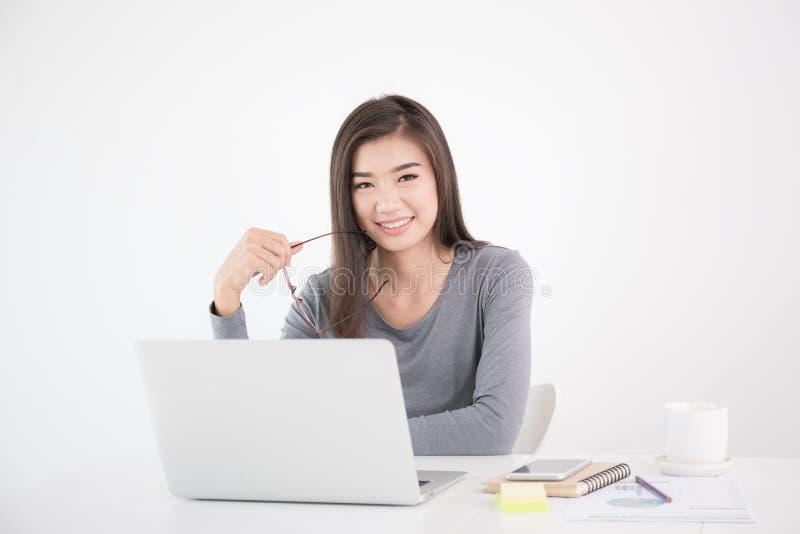 Azjatycka kobieta trzyma szkła w ręce i używa laptop, Żeński smil obrazy stock