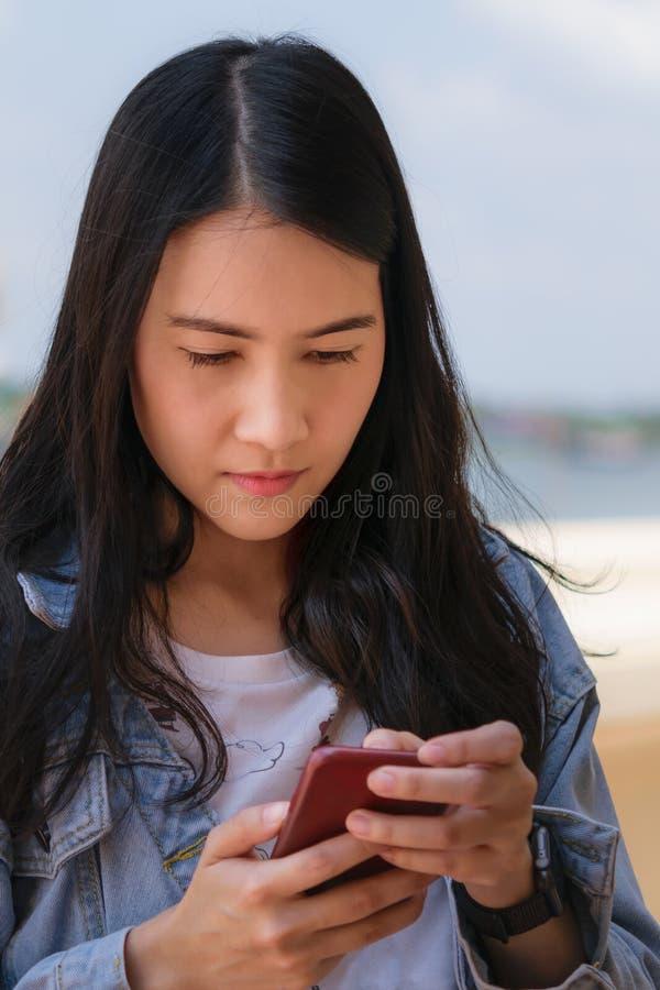 Azjatycka kobieta używa mÄ…drze telefon zdjęcie stock