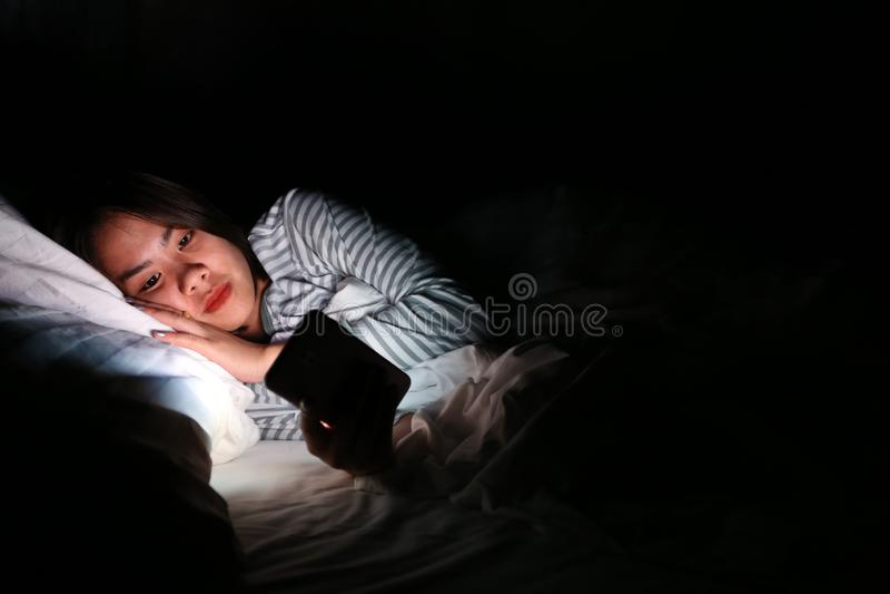 Azjatycka kobieta używa smartphone przy nocą na łóżku w ciemnym pokoju, Używa smartphone w zmroku może być przyczynami oko bólu o obraz stock