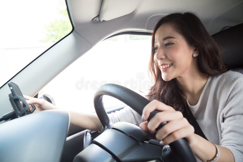 Azjatycka kobieta używa telefon i wysyłający wiadomość podczas jechać samochód obraz stock