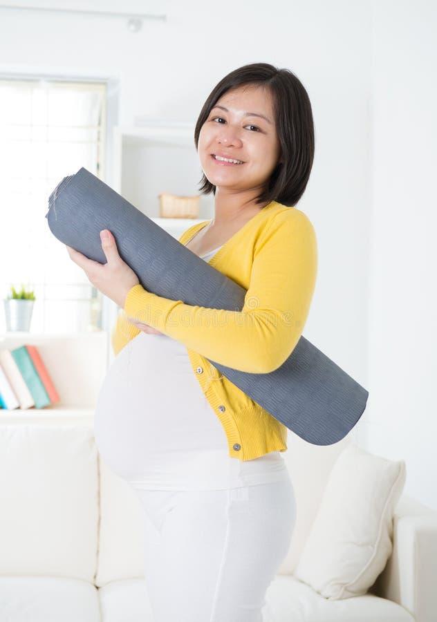 Azjatycka kobieta w ciąży mienia joga mata zdjęcie stock