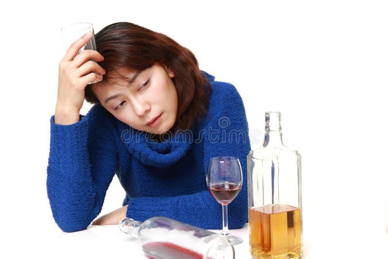 Azjatycka kobieta w depresji pije alkohol obraz royalty free