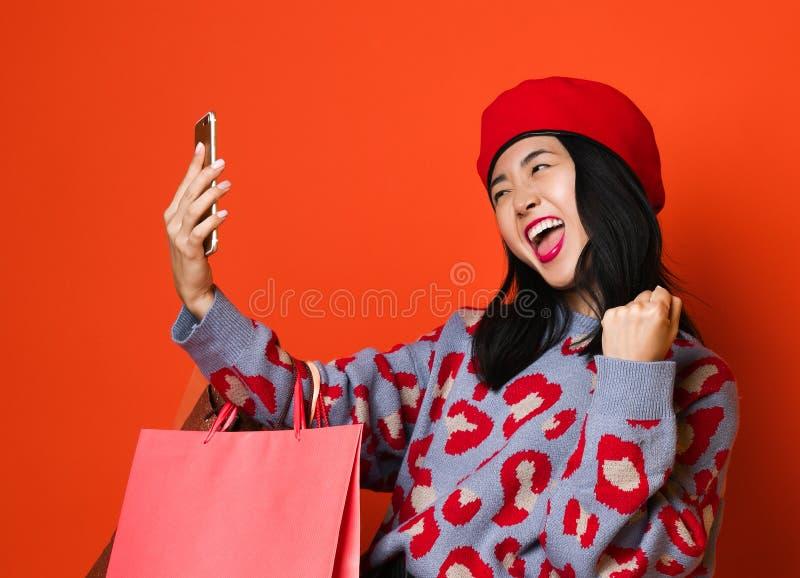 Azjatycka kobieta w eleganckim pulowerze z kolorow? torb? na zakupy i berecie, robi pracowitemu selfie na telefonie po robi? zaku zdjęcia royalty free