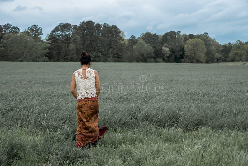 Azjatycka kobieta w polu otaczaj?cym traw? fotografia royalty free