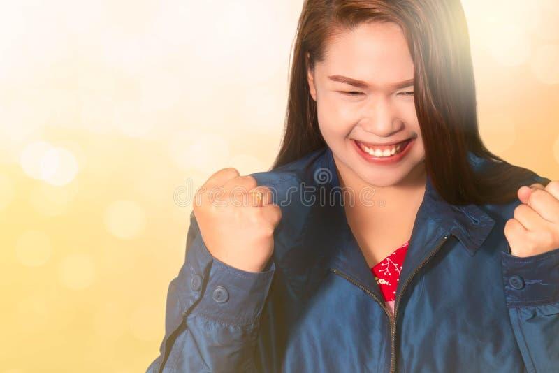 Azjatycka kobieta z pięściami podnosił w górę gesta świętuje zwycięstwo, osiągnięcie i wygranie, pomyślny, zdjęcia royalty free