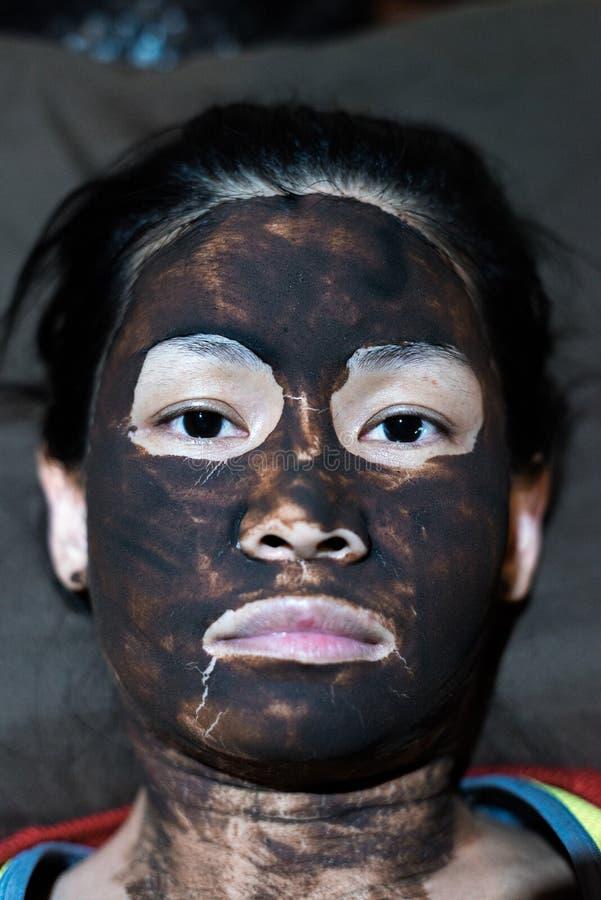 Azjatycka kobiety głowa zakrywająca z borowinową twarzową maską fotografia stock