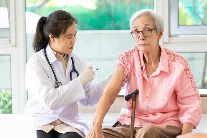 Azjatycka kobiety lekarka z strzykawką robi wtryskowej szczepionki, grypy, grypy w ramieniu lub ręki starsza kobieta, potomstwo p zdjęcie stock