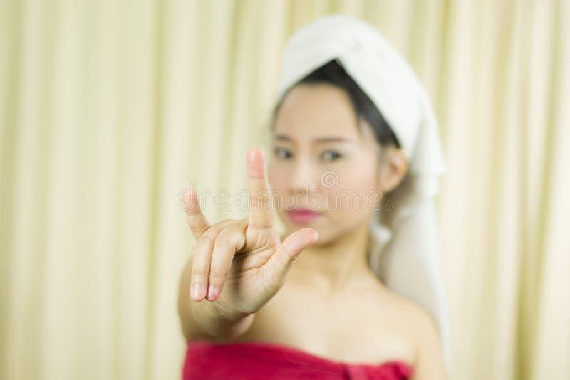 Azjatycka kobiety odzie? sp?dnica zakrywa? jej pier? po obmycie w?osy, Zawijaj?cego w r?cznikach Po tym jak prysznic i dawa? gest zdjęcia stock