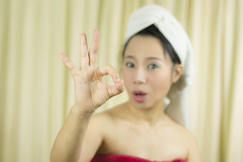 Azjatycka kobiety odzie? sp?dnica zakrywa? jej pier? po obmycie w?osy, Zawijaj?cego w r?cznikach Po tym jak prysznic i dawa? gest zdjęcia royalty free