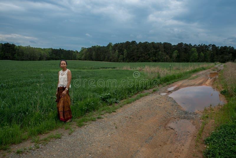 Azjatycka kobiety pozycja na drodze gruntowej w polu obraz stock