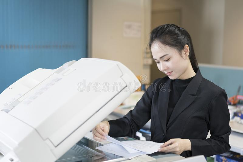 Azjatycka kobiety sekretarka używa odbitkową maszynę zdjęcia stock