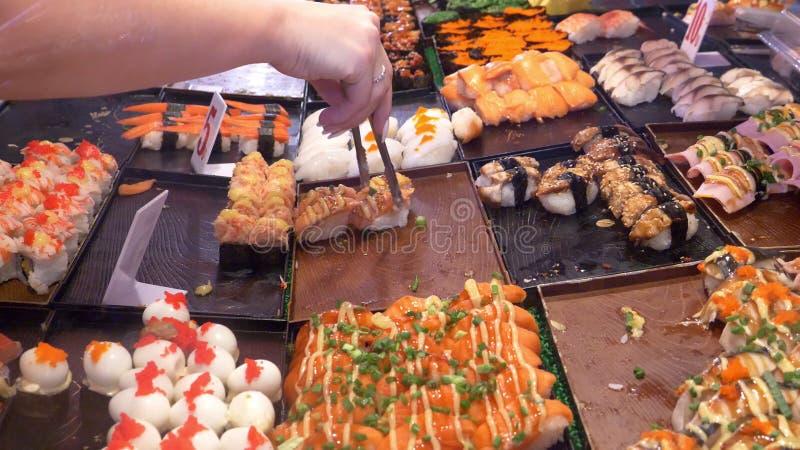 Azjatycka kuchnia, karmowy pojęcie zakończenie ręki z tongs wybierają suszi na noc rynku w ulicie obrazy royalty free