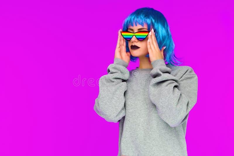 Azjatycka lesbian dziewczyna w błękitnych peruki i tęczy okularów przeciwsłonecznych spojrzeniach strona na różowym tle obraz stock