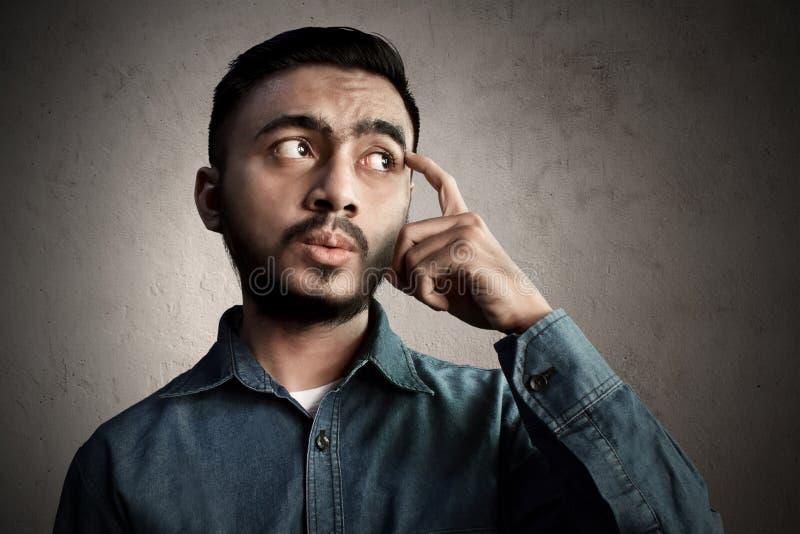 Azjatycka mężczyzna myśl i wprawiać w zakłopotanie zdjęcia stock