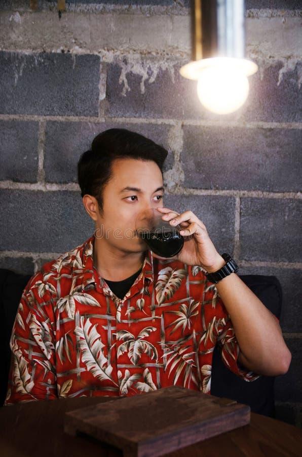 Azjatycka mężczyzna odzieży Hawaii koszula pije czarną kawę obrazy royalty free