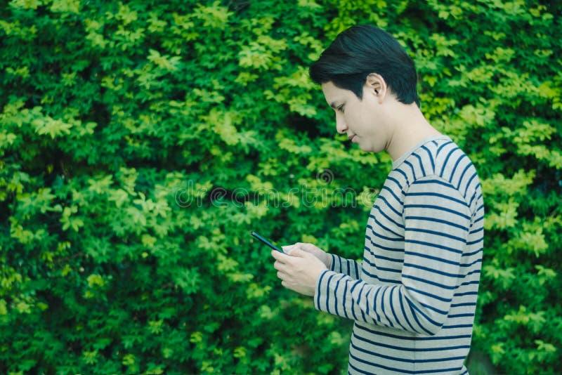 Azjatycka mężczyzna pozycja i używać smartphone zdjęcia royalty free