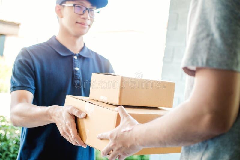 Azjatycka mężczyzna ręka akceptuje dostawę boksuje od fachowego deliveryman w domu zdjęcie stock