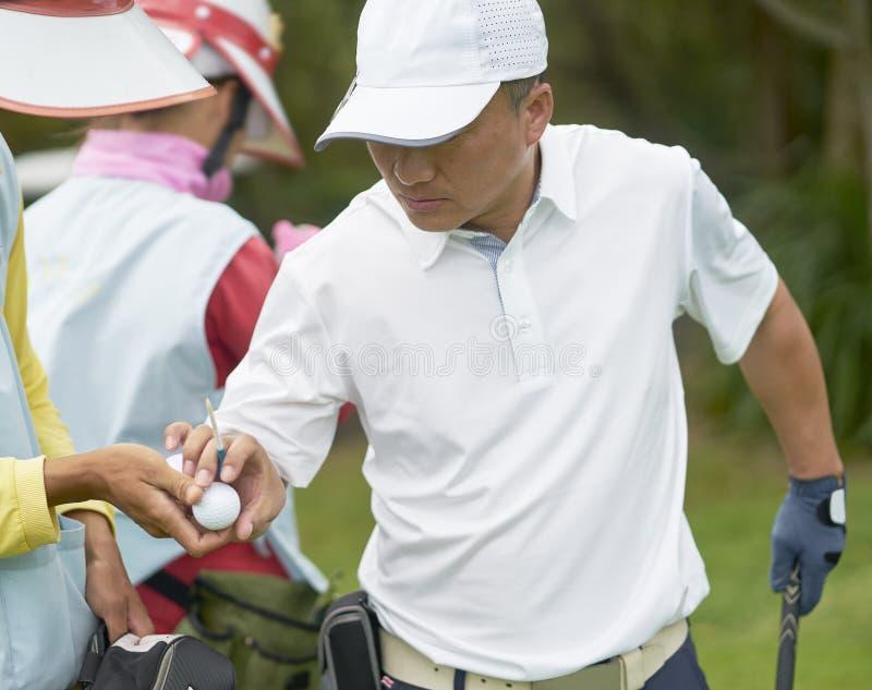 Azjatycka mężczyzna zrywania piłka od jego caddie gdy bawić się golfa w kursie zdjęcie stock
