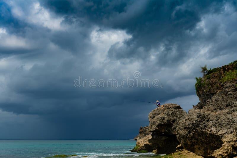 Azjatycka mężczyzny łapania ryba na skale w burzy obrazy stock