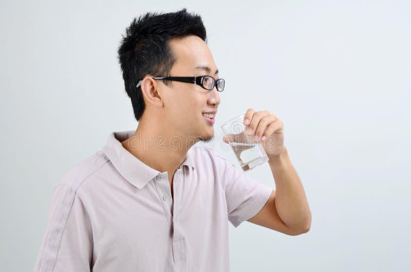 Azjatycka męska pije woda mineralna zdjęcia stock