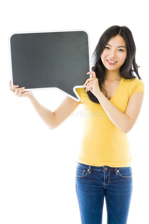 Azjatycka młoda kobieta trzyma pustego mowa bąbel zdjęcia stock