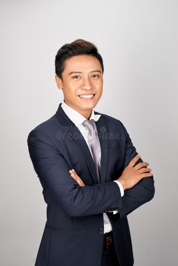 Azjatycka młoda przystojna biznesmen pozycja zbroi krzyżuje, ono uśmiecha się szczęśliwy, patrzejący kamerę obrazy royalty free