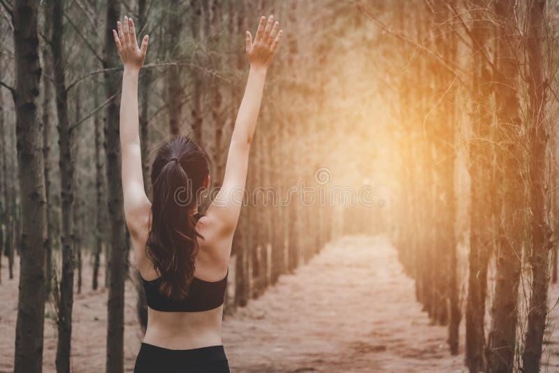 Azjatycka m?oda kobieta robi joga i rozprzestrzenia r?ki w lesie Popiera widok Natura i Zdrowy sporta poj?cie Wdycha świeże powie obrazy stock