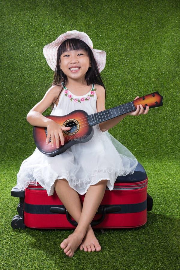 Azjatycka Mała Chińska dziewczyna bawić się z gitarą zdjęcie royalty free