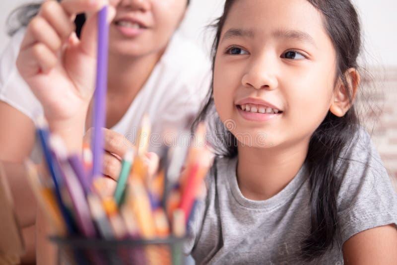 Azjatycka mała dziewczynka i kobieta wybiera kolor dla malować obraz stock