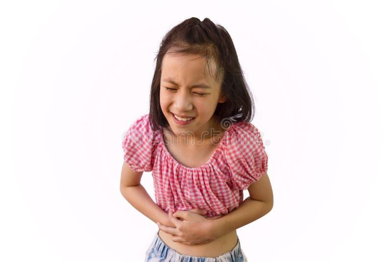Azjatycka mała dziewczynka jest bolesnym żołądka obolałością odizolowywającym na białym tle, dziecku ma zatrucie pokarmowe, choro fotografia royalty free