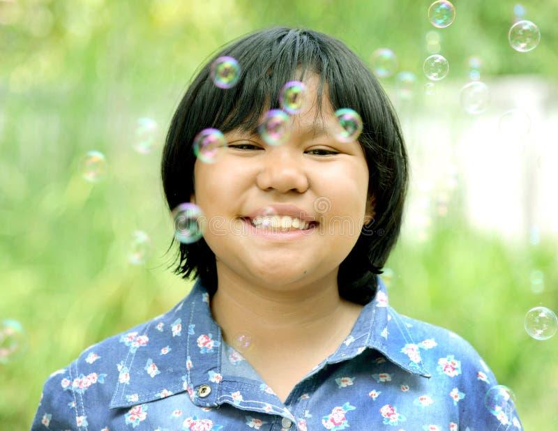 Azjatycka mała dziewczynka jest uśmiechnięta z mydlanymi bąblami wokoło obraz stock