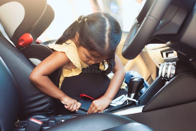 Azjatycka małe dziecko dziewczyna przymocowywa ochrona pasek ona obraz stock