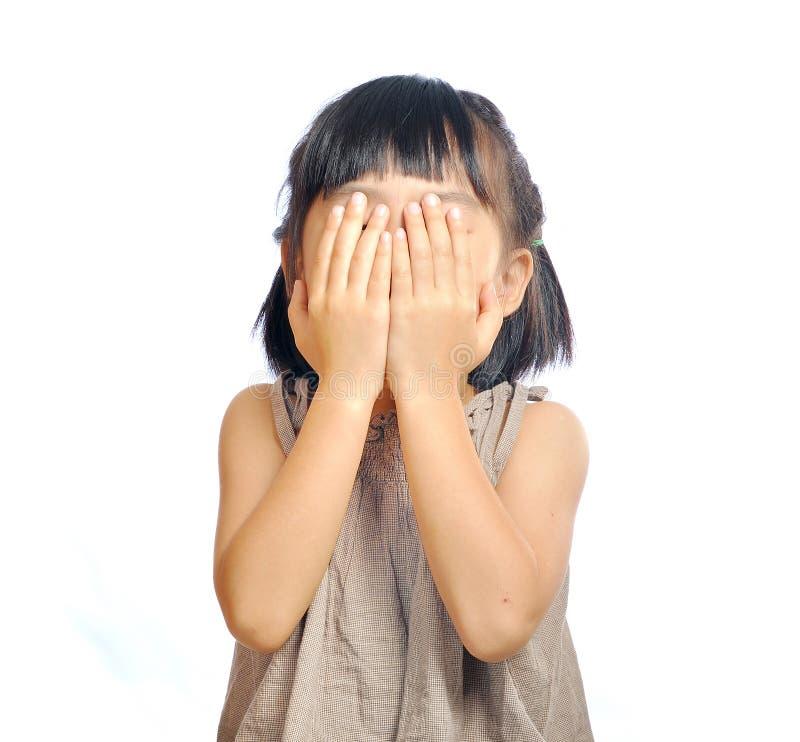 Azjatycka małej dziewczynki pokrywa z jej ręką odizolowywającą w bielu jej twarz zdjęcie royalty free