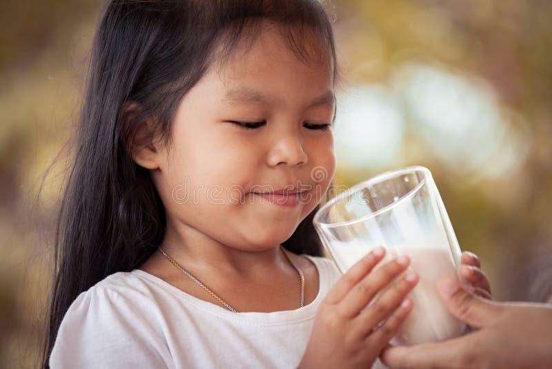 Azjatycka małej dziewczynki próba pić mleko od szkła obraz royalty free