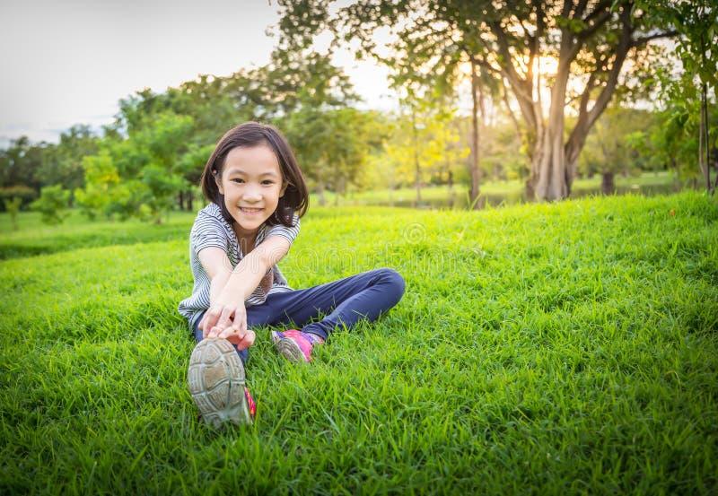 Azjatycka ma?a dziewczynka ?wiczy przy plenerowym parkiem na gazonie jest medytacji praktyk?, dziecka ?wiczenie w naturze w ranku zdjęcia stock