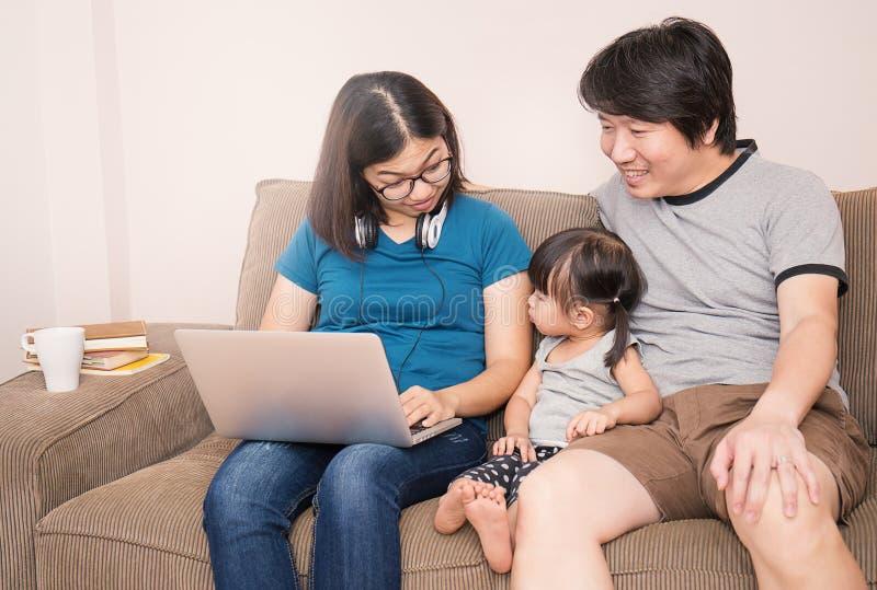 Azjatycka mama i tata używa komputer z ich córką zdjęcia stock