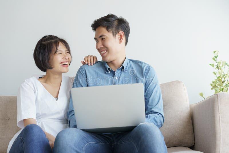 Azjatycka miłości para siedzi kanapę i używa laptop są uśmiechnięci szczęśliwie w domu obraz stock