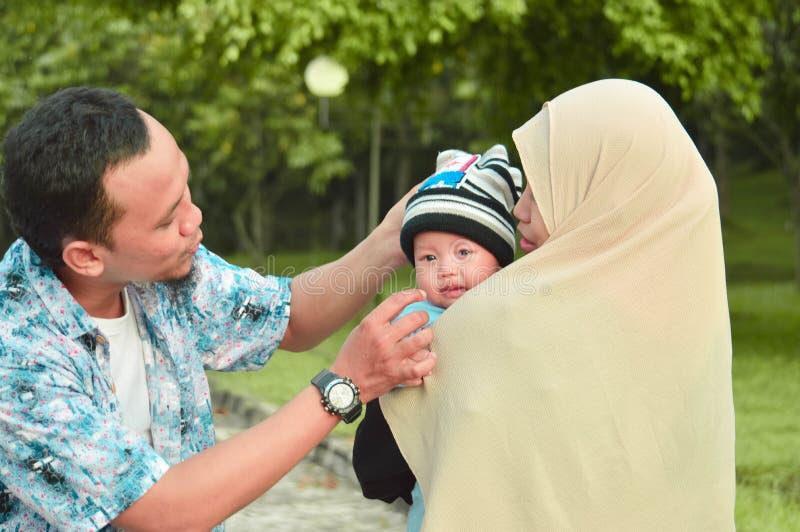 Azjatycka muzułmańska hijabi matka, ojciec i chodzimy przez parka z synem w spacerowiczu podczas gdy jego mama bierze opiekę jej  obraz stock