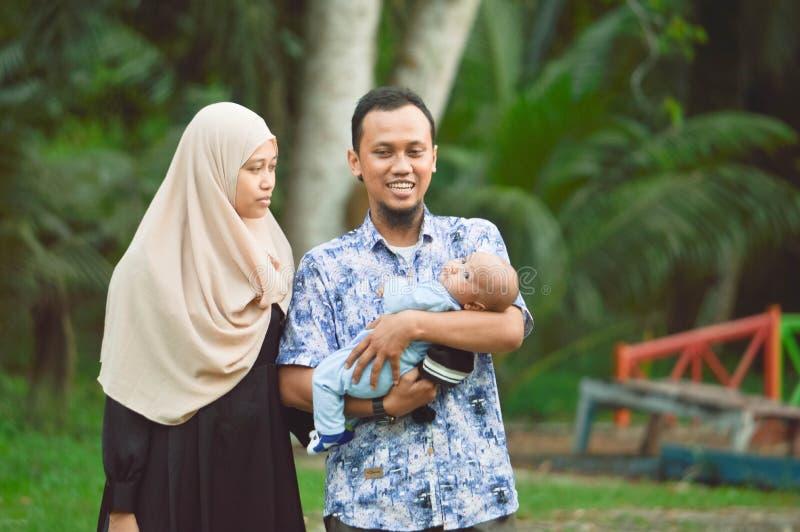 Azjatycka muzułmańska hijabi matka, ojciec i chodzimy przez parka z synem w spacerowiczu podczas gdy jego mama bierze opiekę jej  obrazy stock